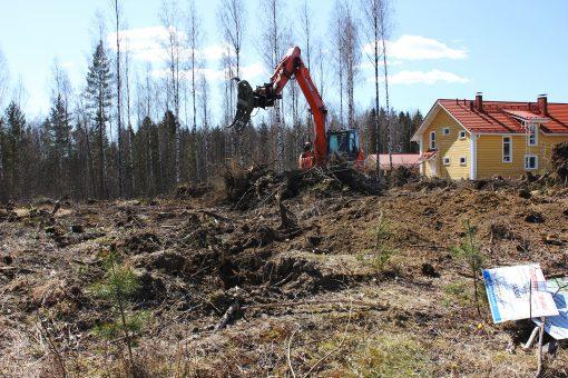 Kaivuri muokkaa maata tontilla, joka on myyty.